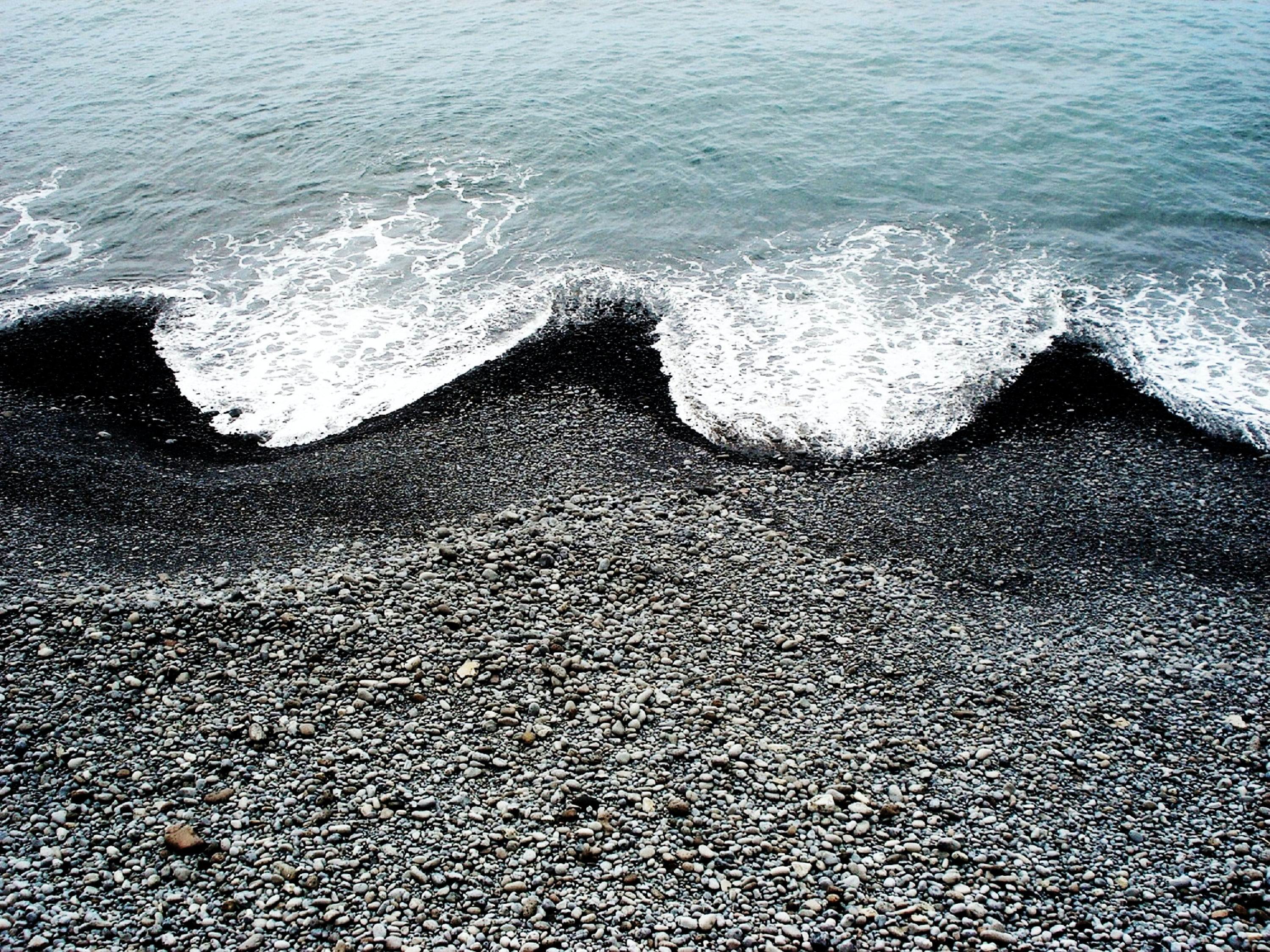 ocean waves hugging black beach sand
