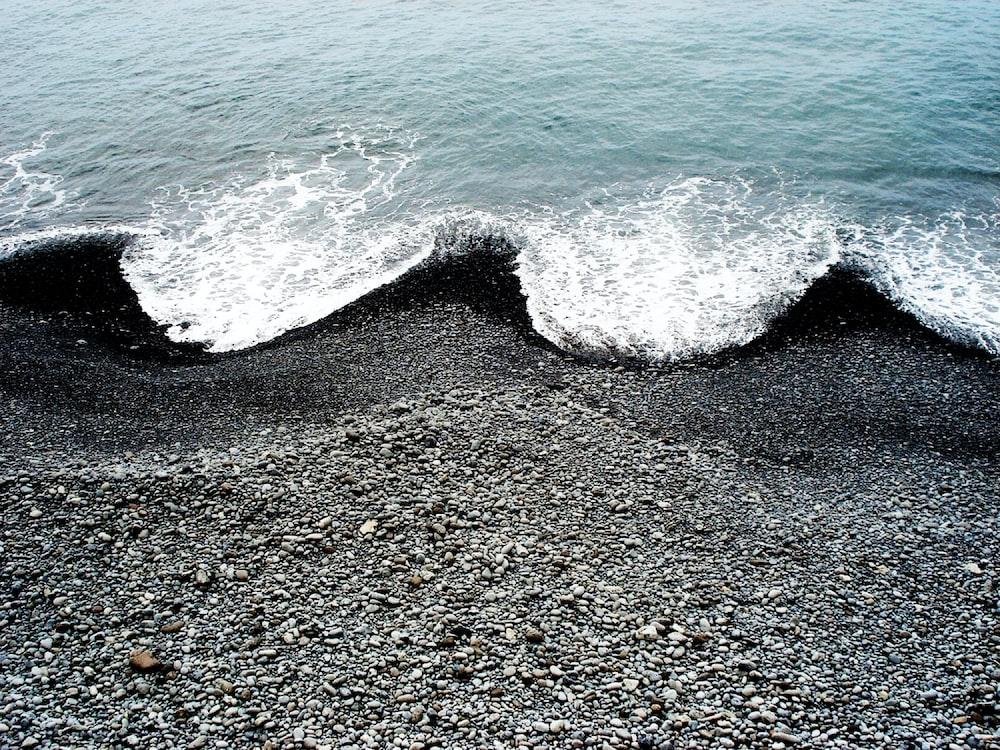 ocean waves hugging black beach sand