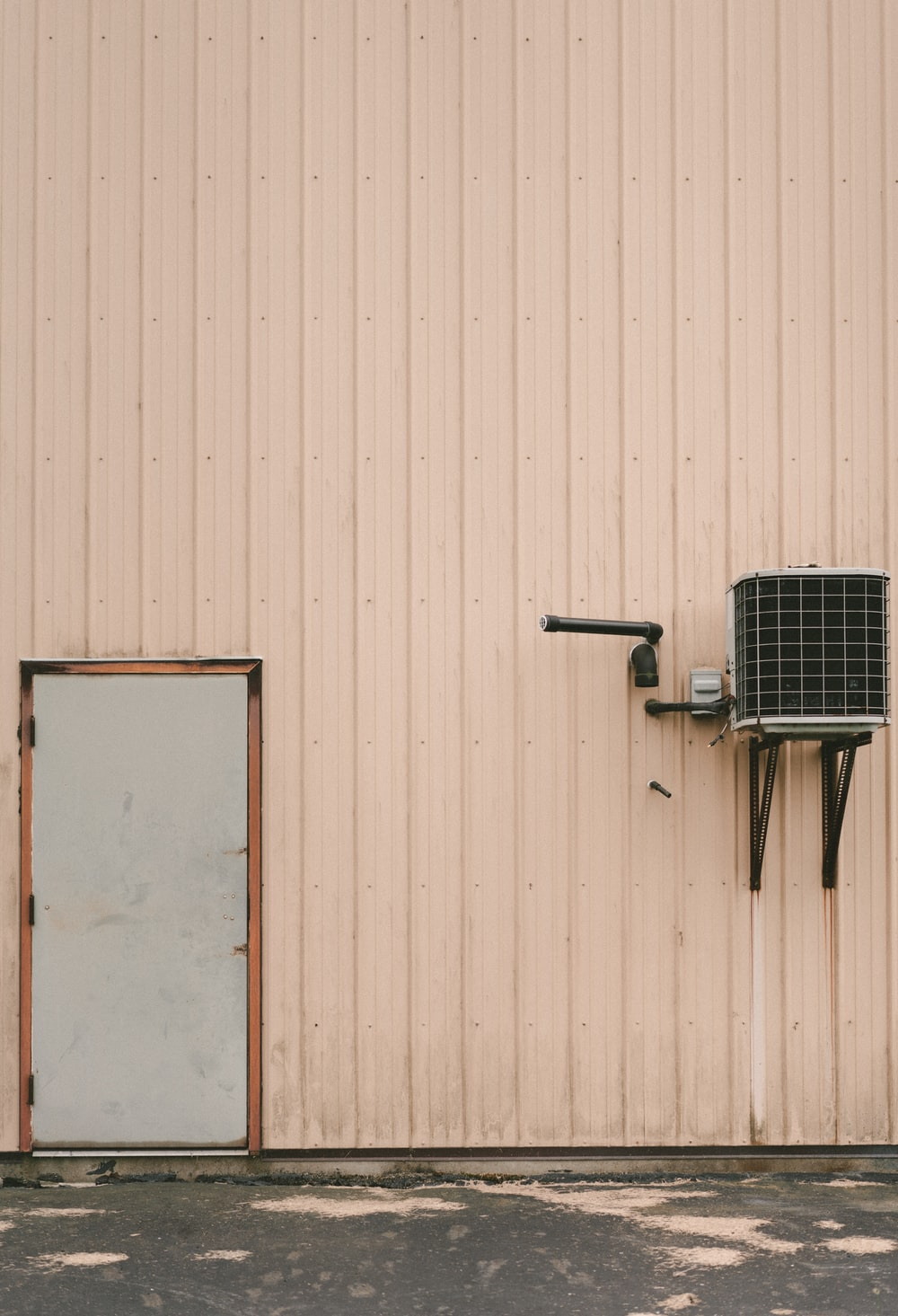 gray air condenser beside gray closed door