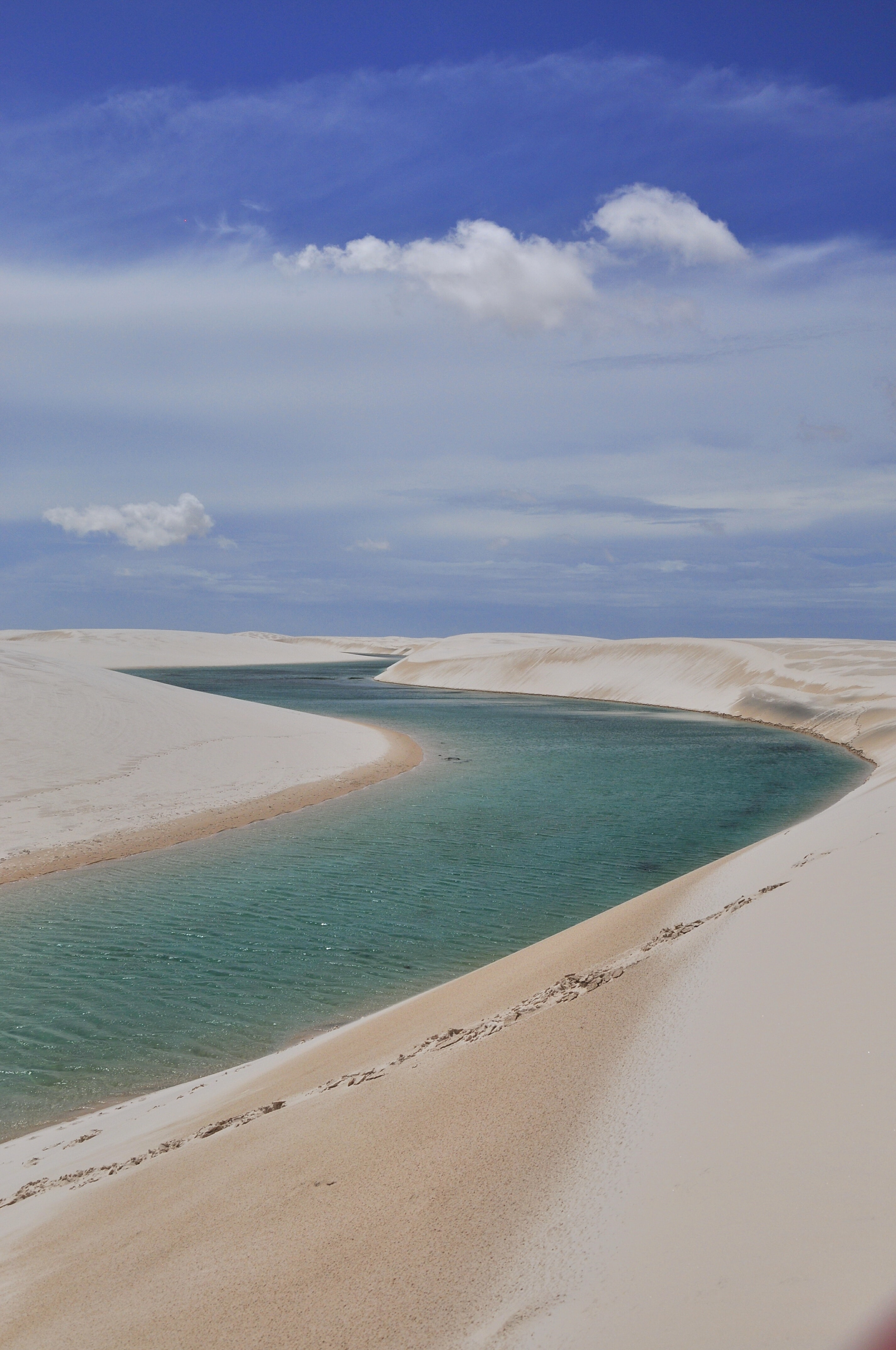 body of water between sand under cloudy sky