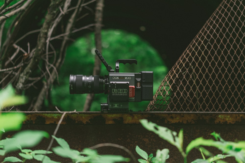 black studio camera on top on brown bar