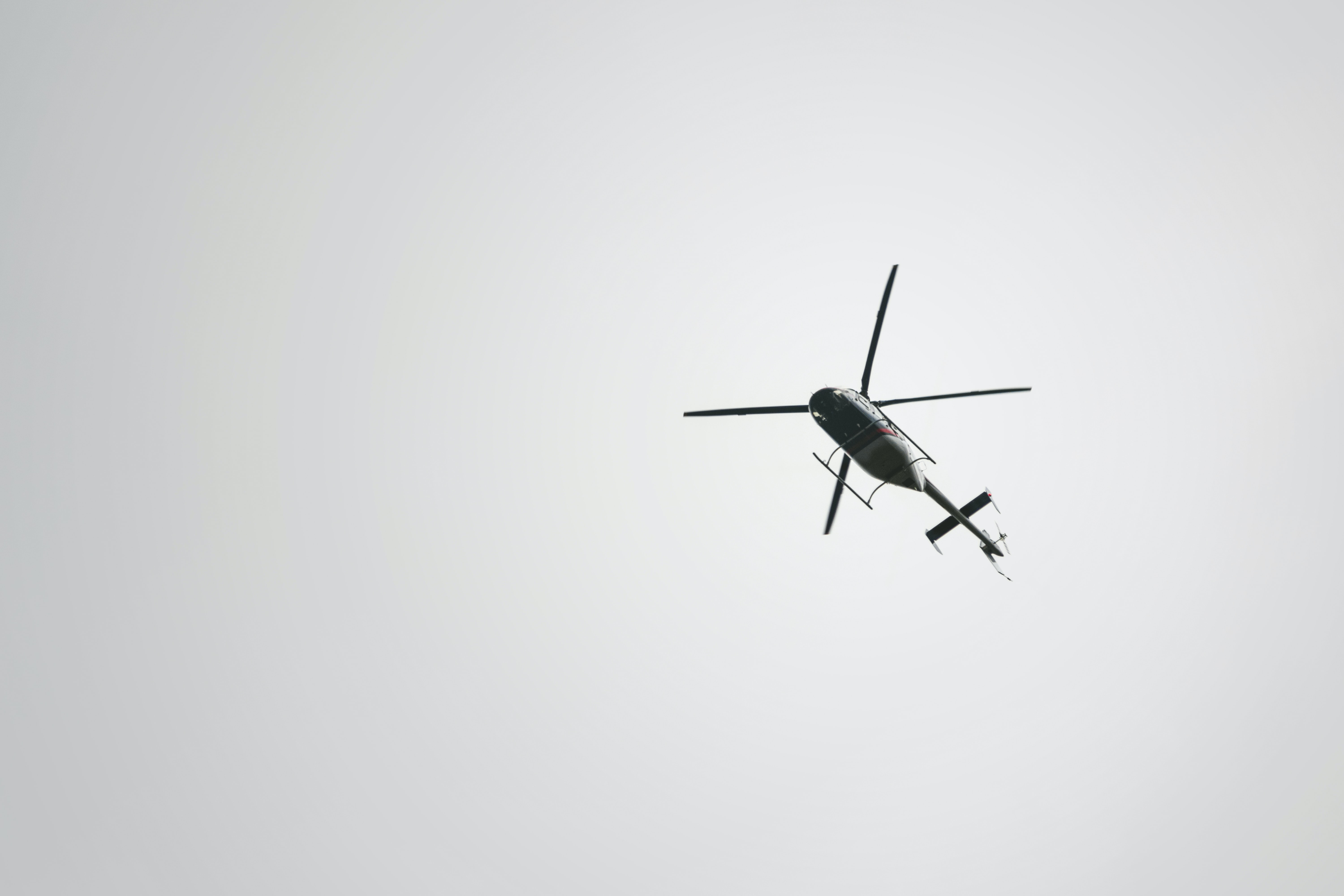 worms-eye-view of flying black helicopter