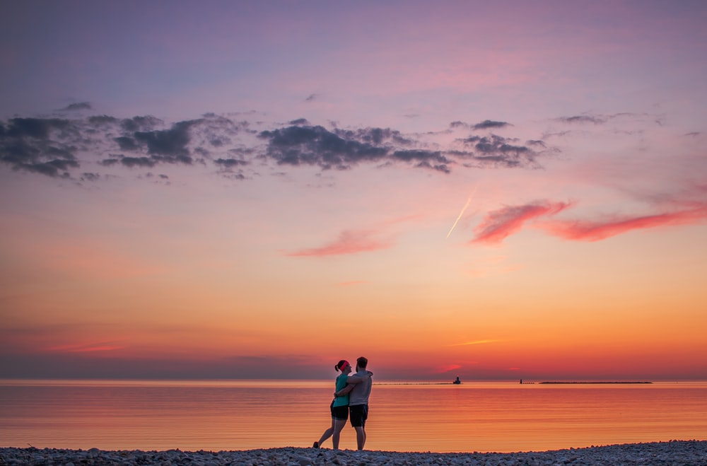 couple hugging each other near seashore