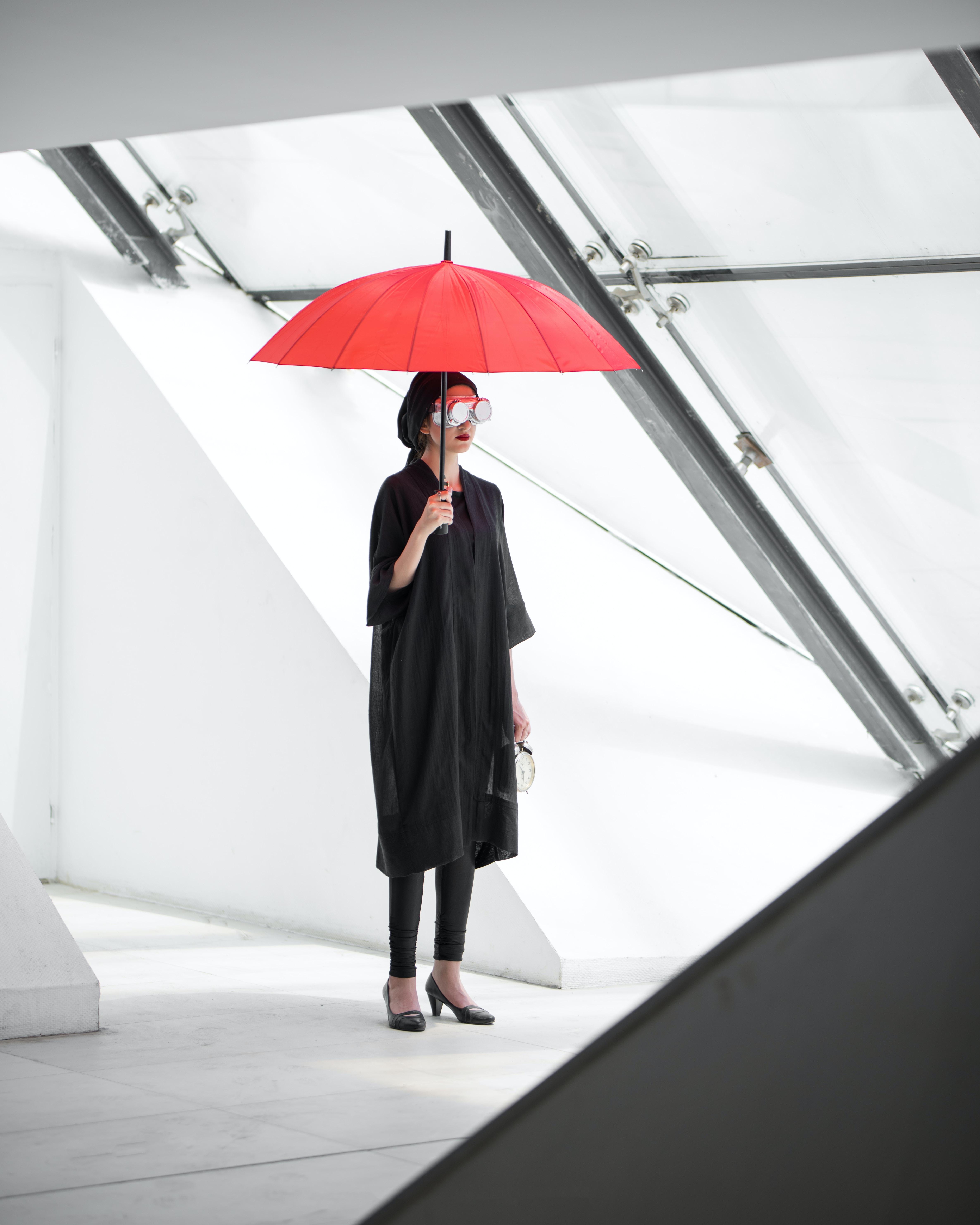 woman standing holding umbrella inside building