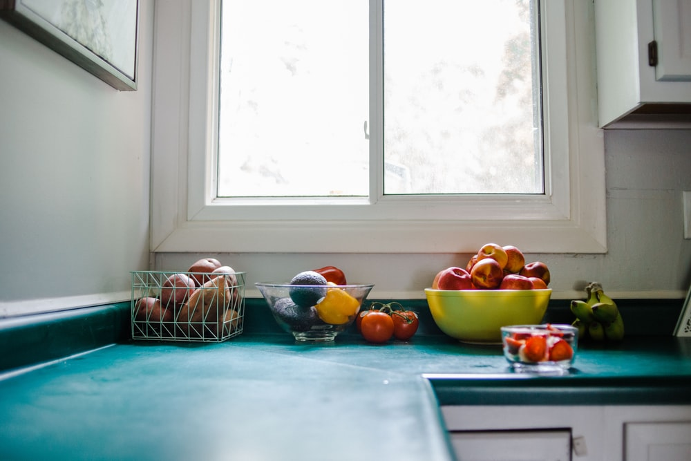 bowl of red apple on blue kitchen cabinet