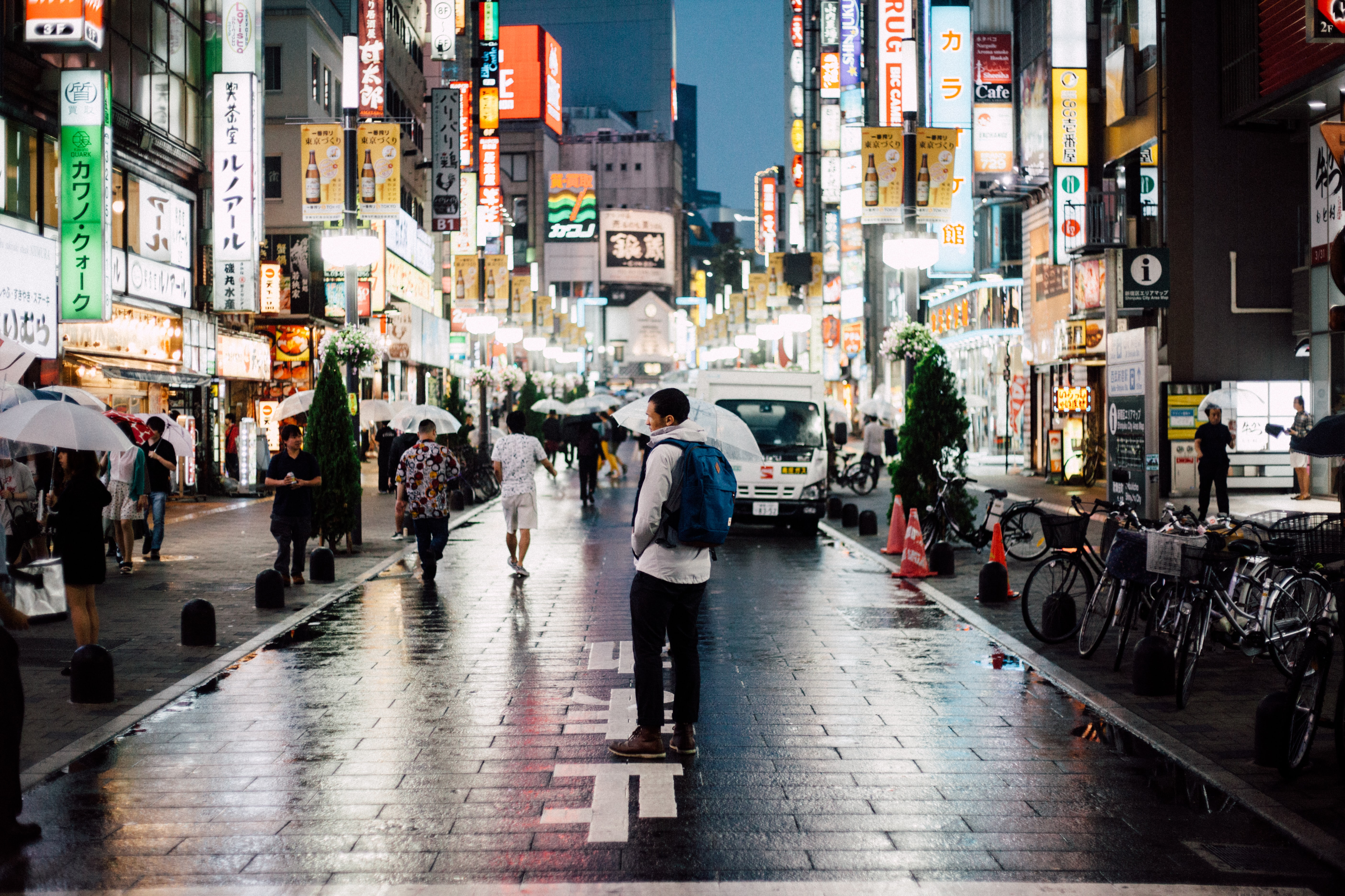 man with backpack standing on street during night time