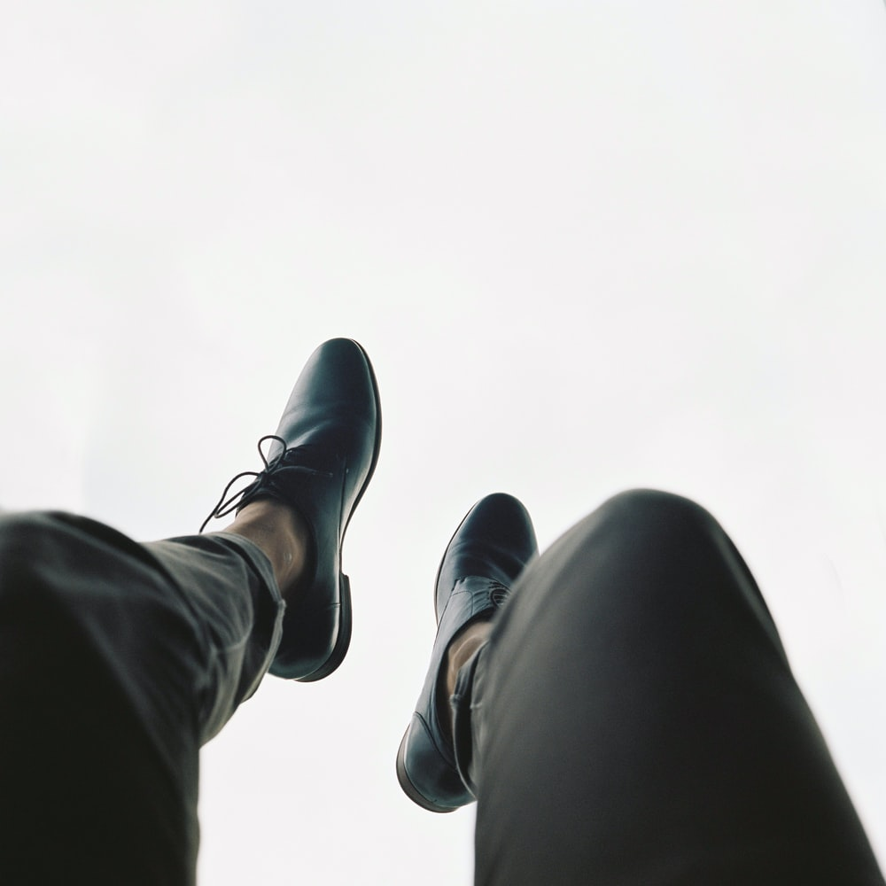 person wearing pair of black leather dress shoes