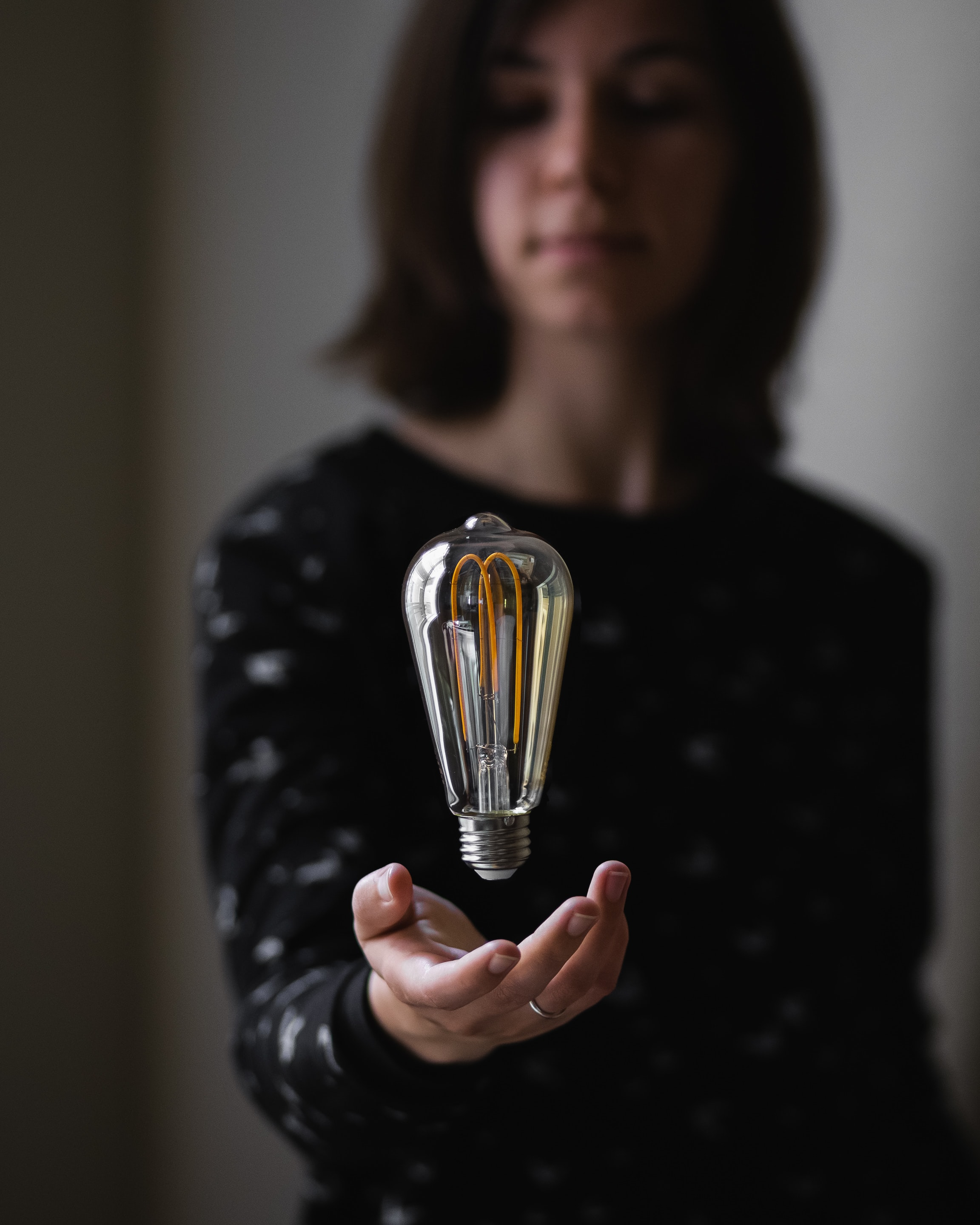 person trying to hold clear light bulb