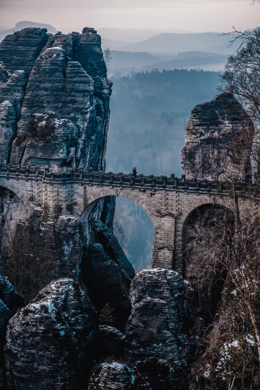 arc bridge beside mountain