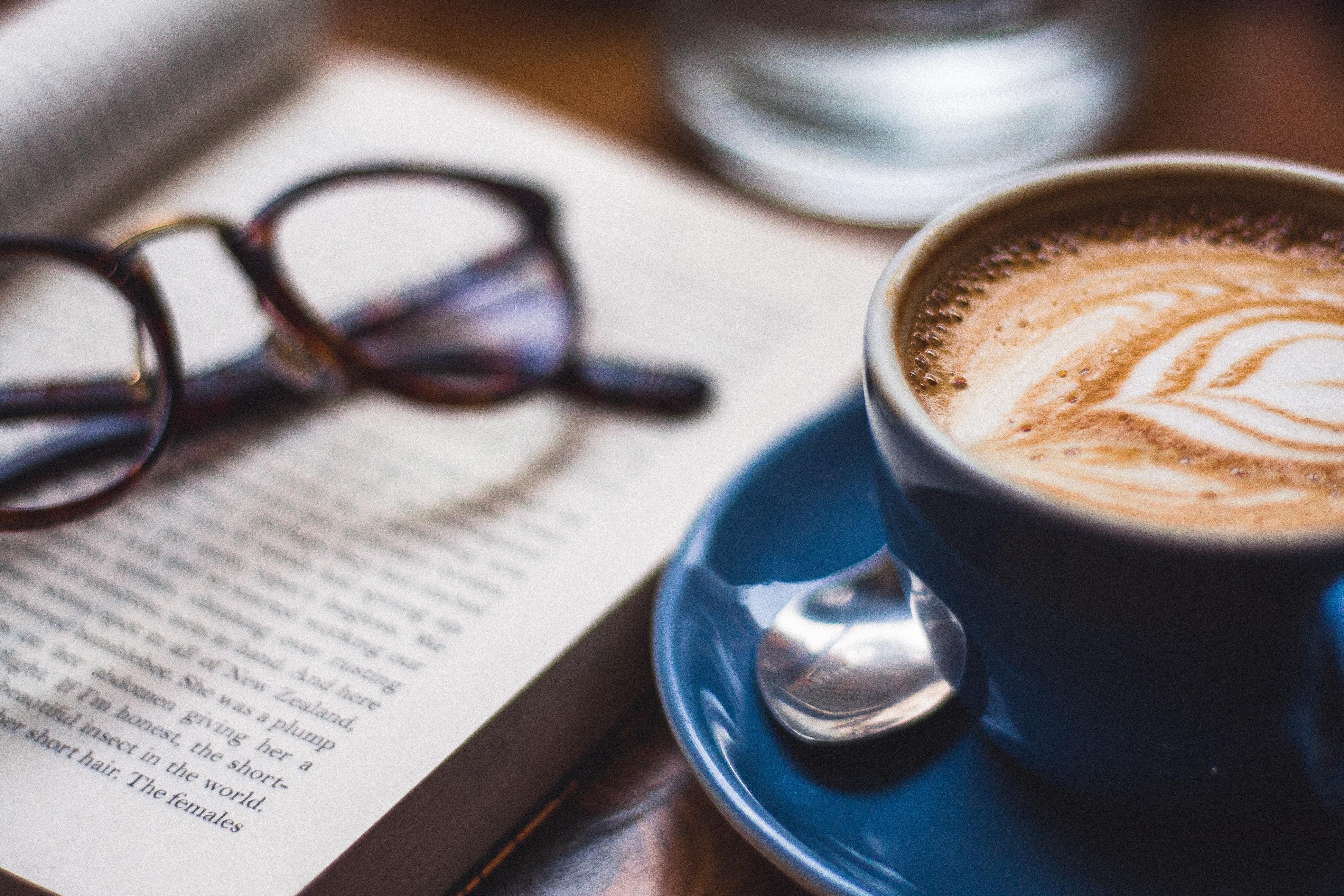 black framed eyeglasses on book beside cappuccino