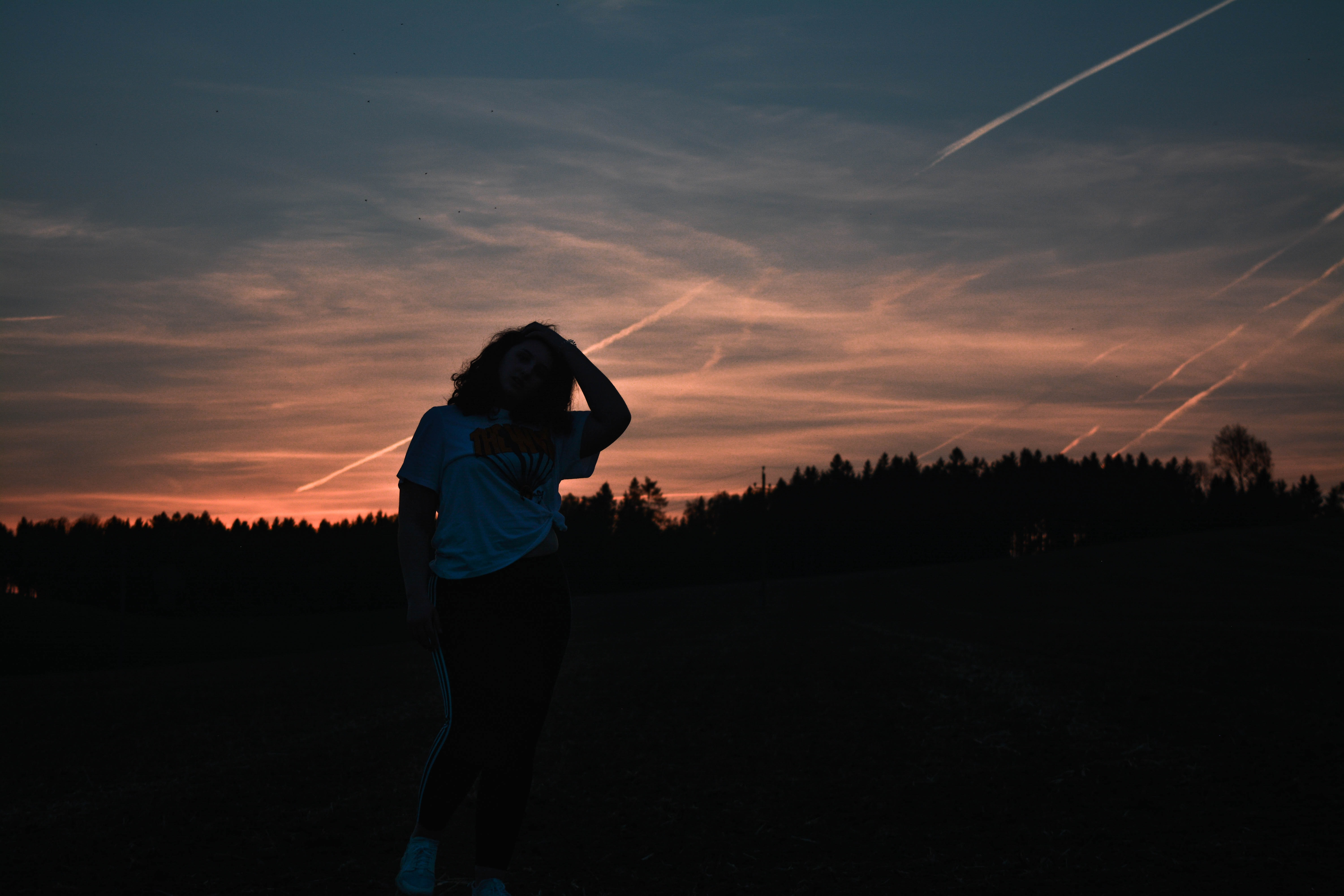 silhouette of woman in front of falling stars at golden hour