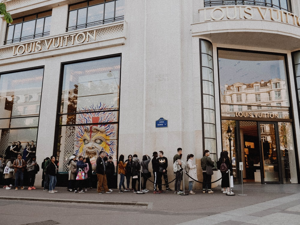 people queuing beside Louis Vuitton store