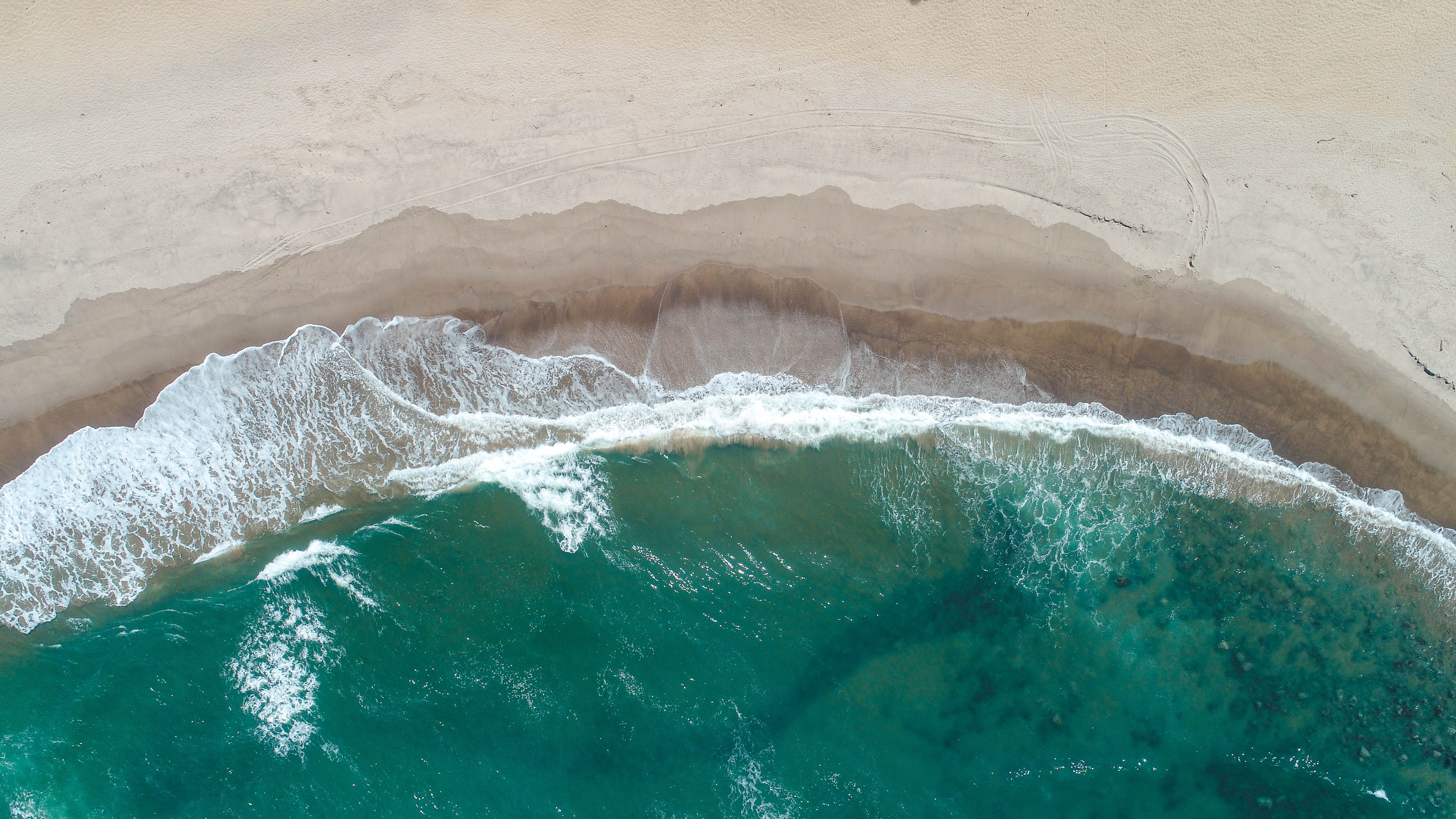 ocean waves hitting shore aerial photo