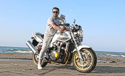 man riding on motorcycle on shoreline honda teams background