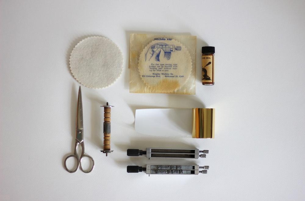 silver scissors beside brown rod
