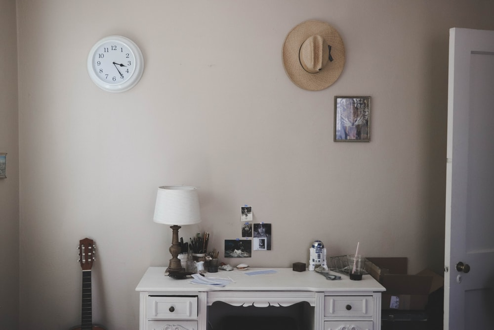 table lamp on knee-hole desk beside closed door
