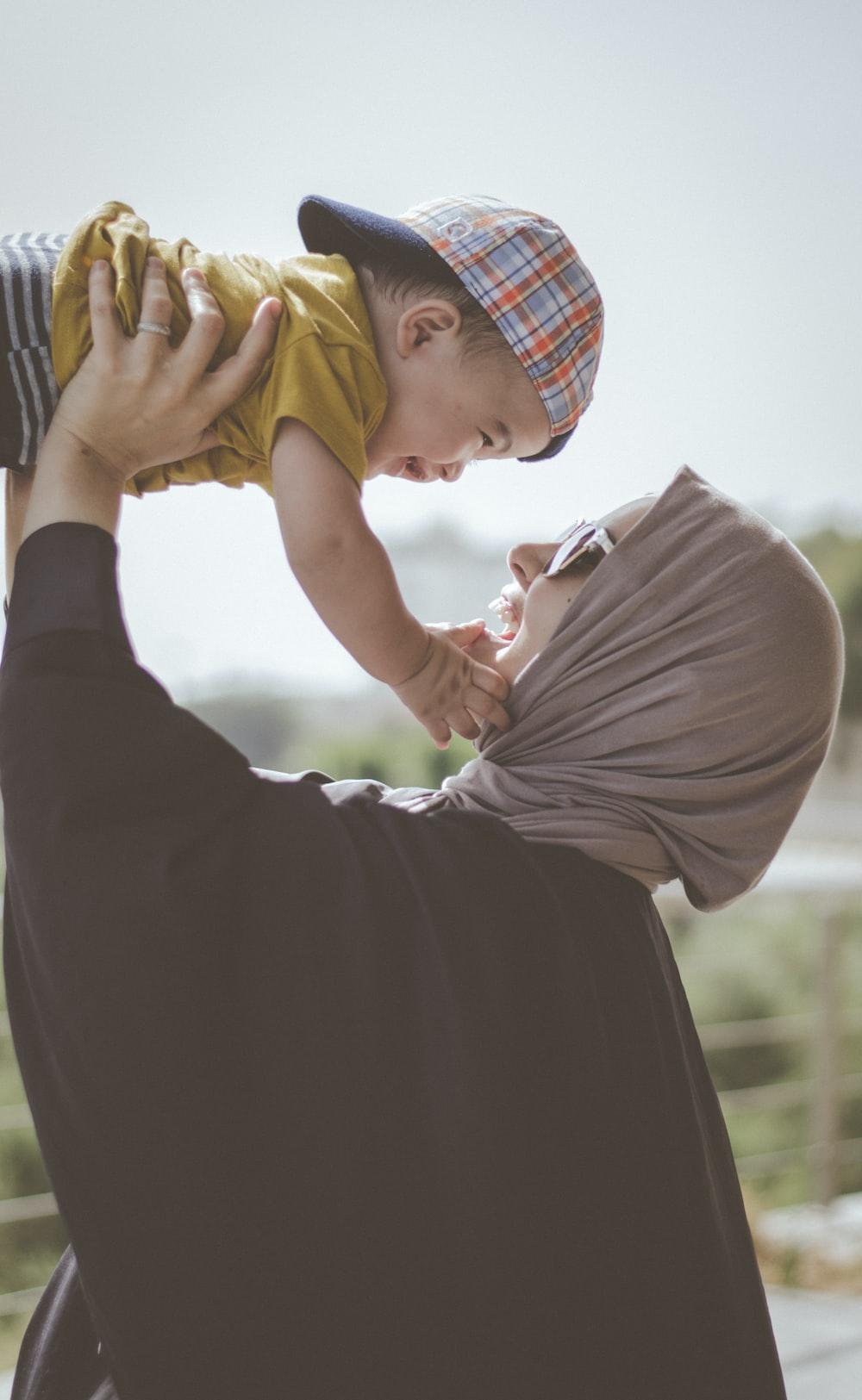 woman holding boy during daytime