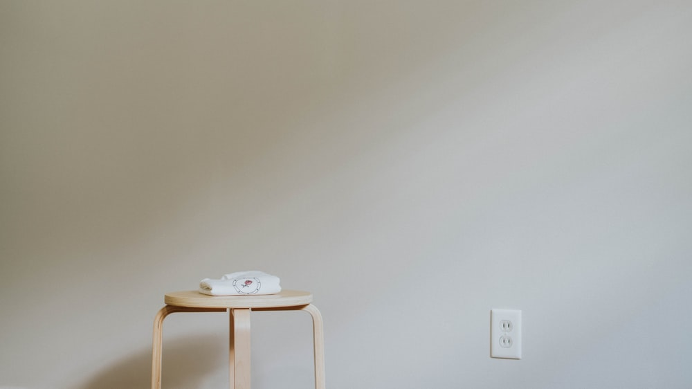 round brown wooden stool near outlet