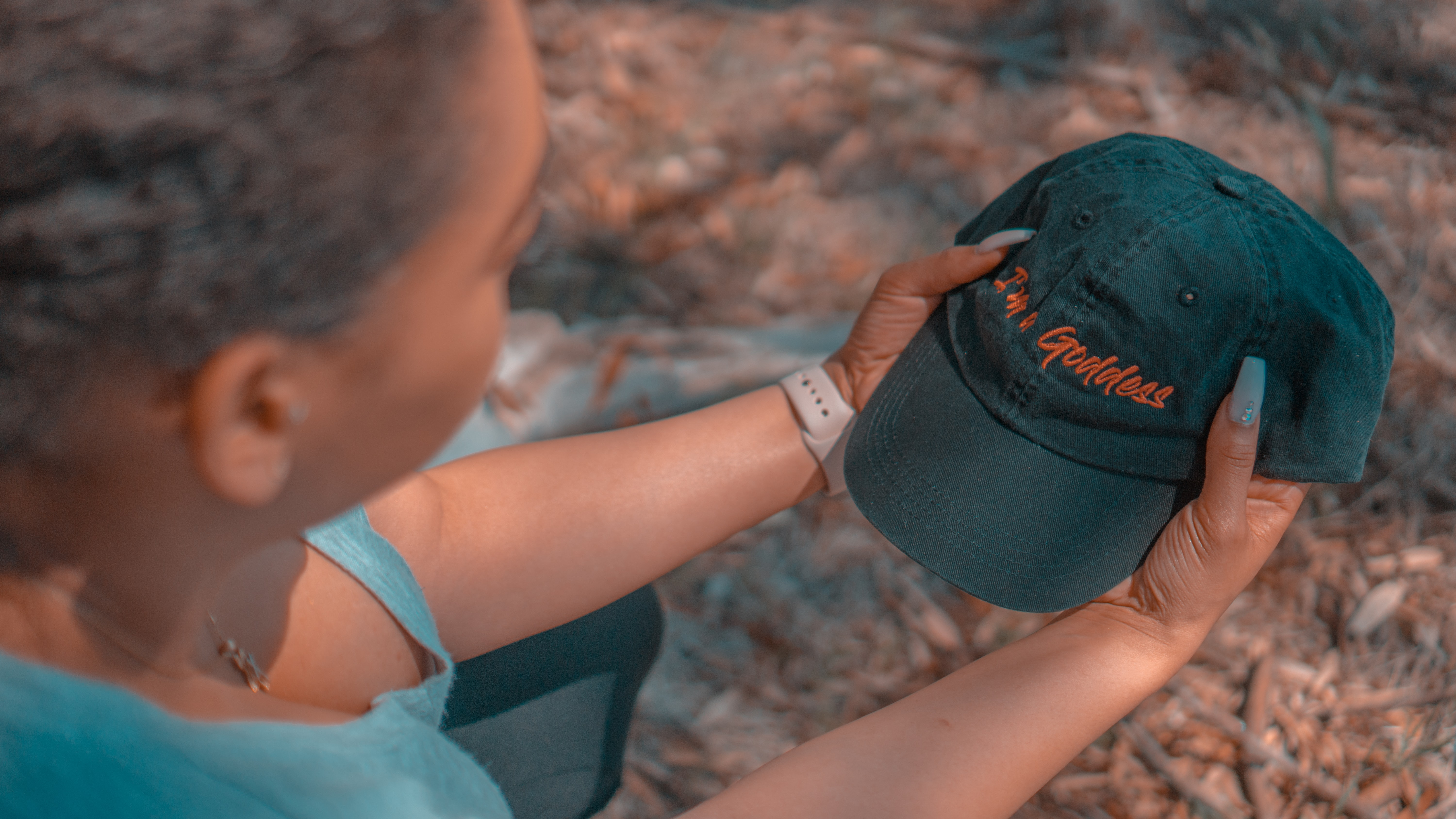 woman holding teal curved-brim cap