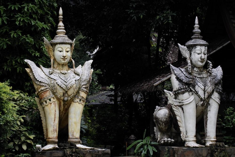 two man head statues near trees