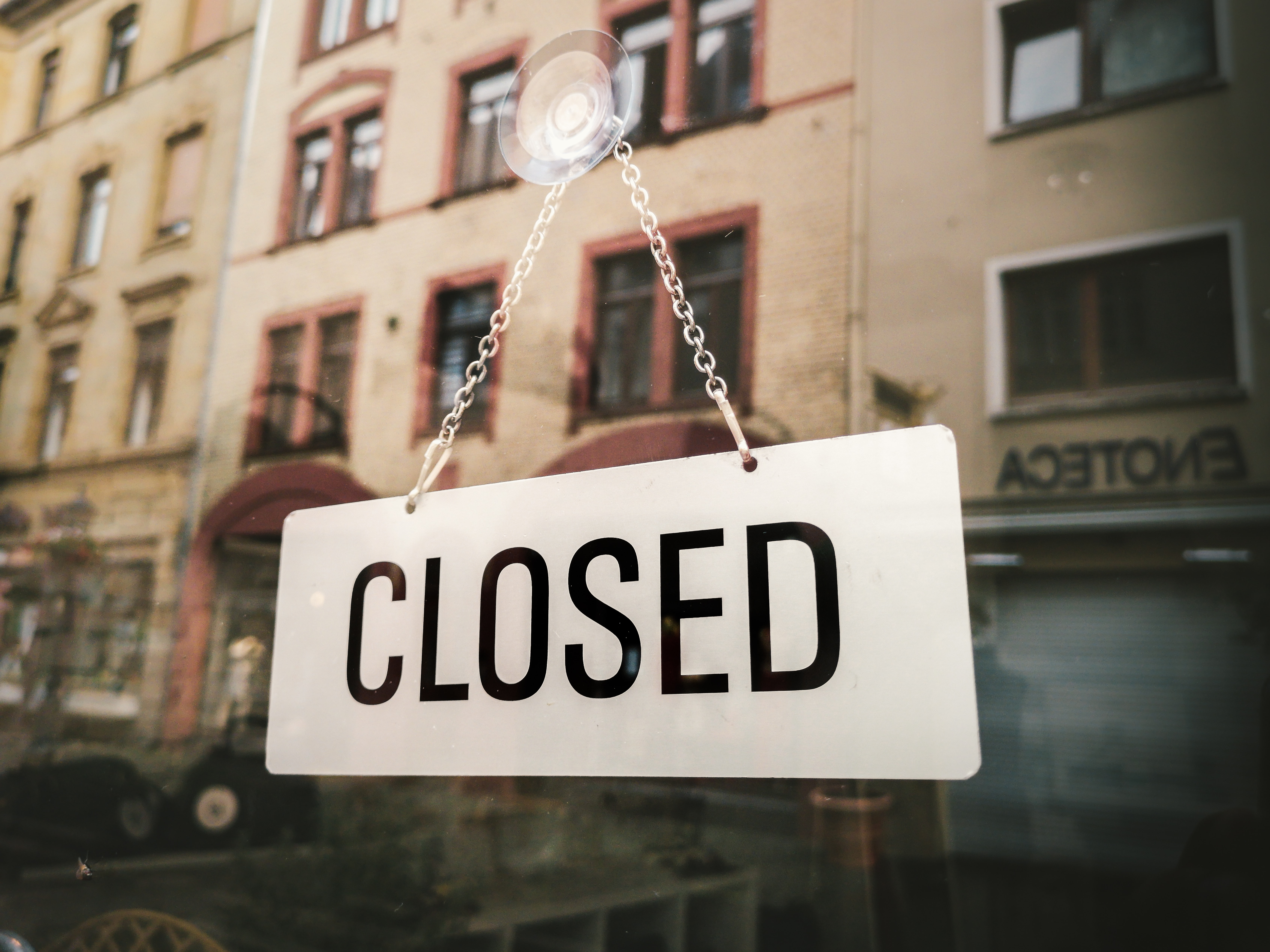 white closed sign hanging on glass