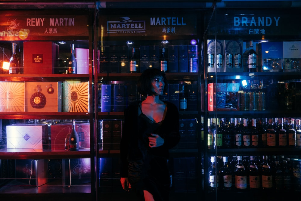 woman standing beside liquor store