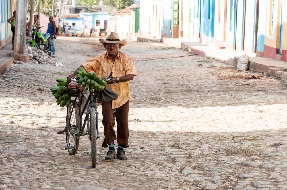man walking on walkway while holding his bicycle