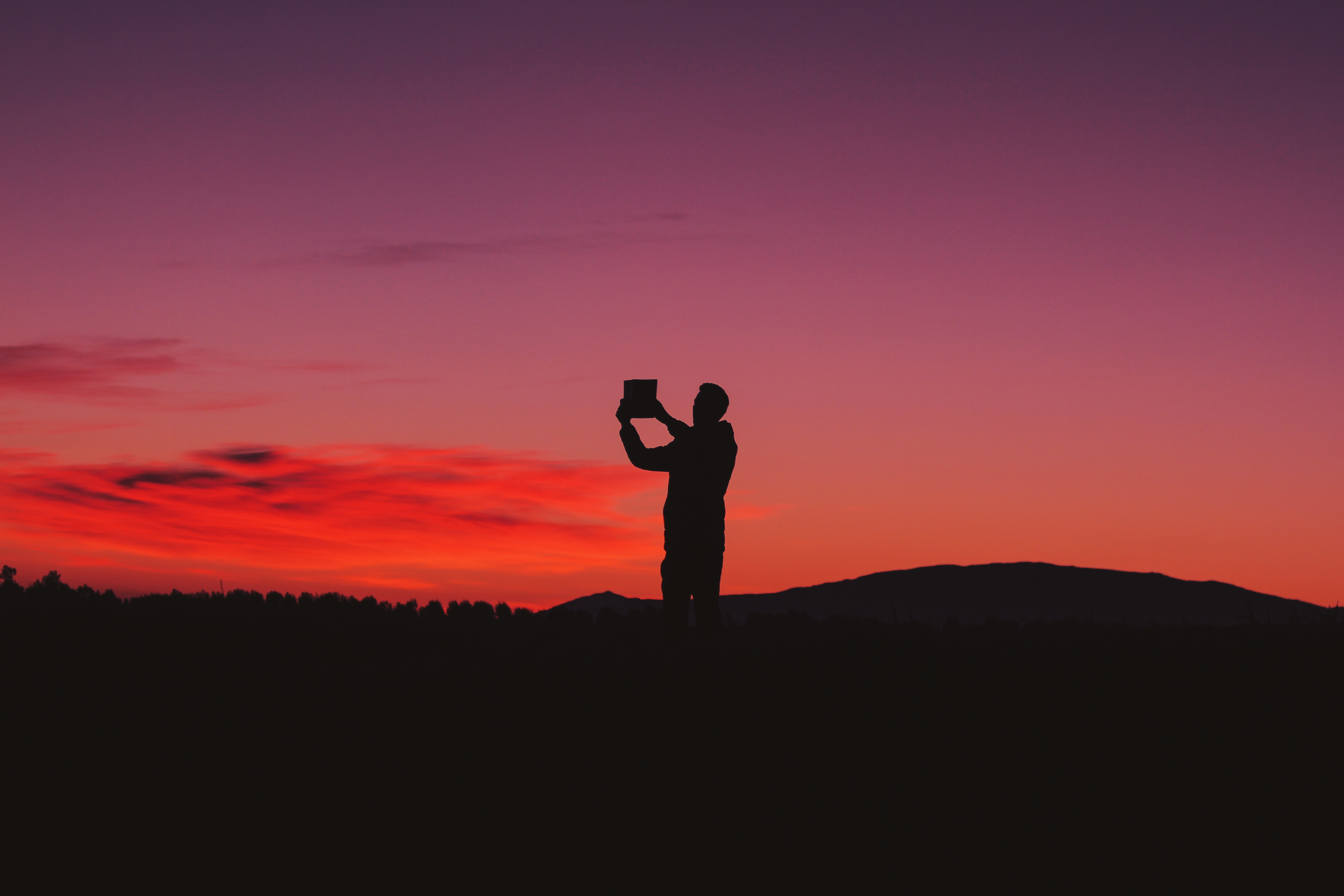 silhouette photo of man on hill