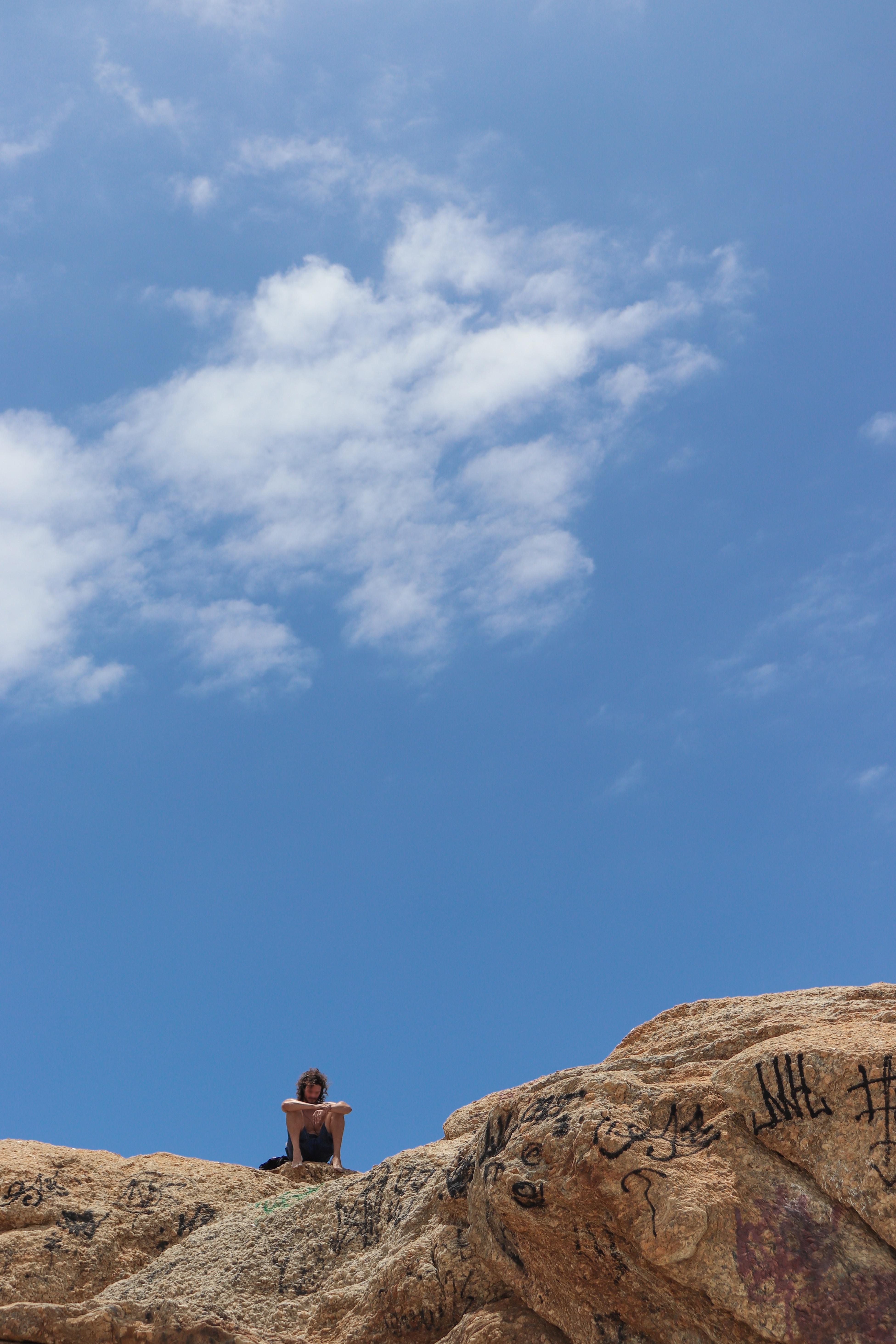 man sitting on rock formation under clear blue sky