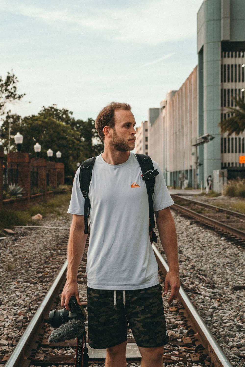 man standing on train rail at daytime
