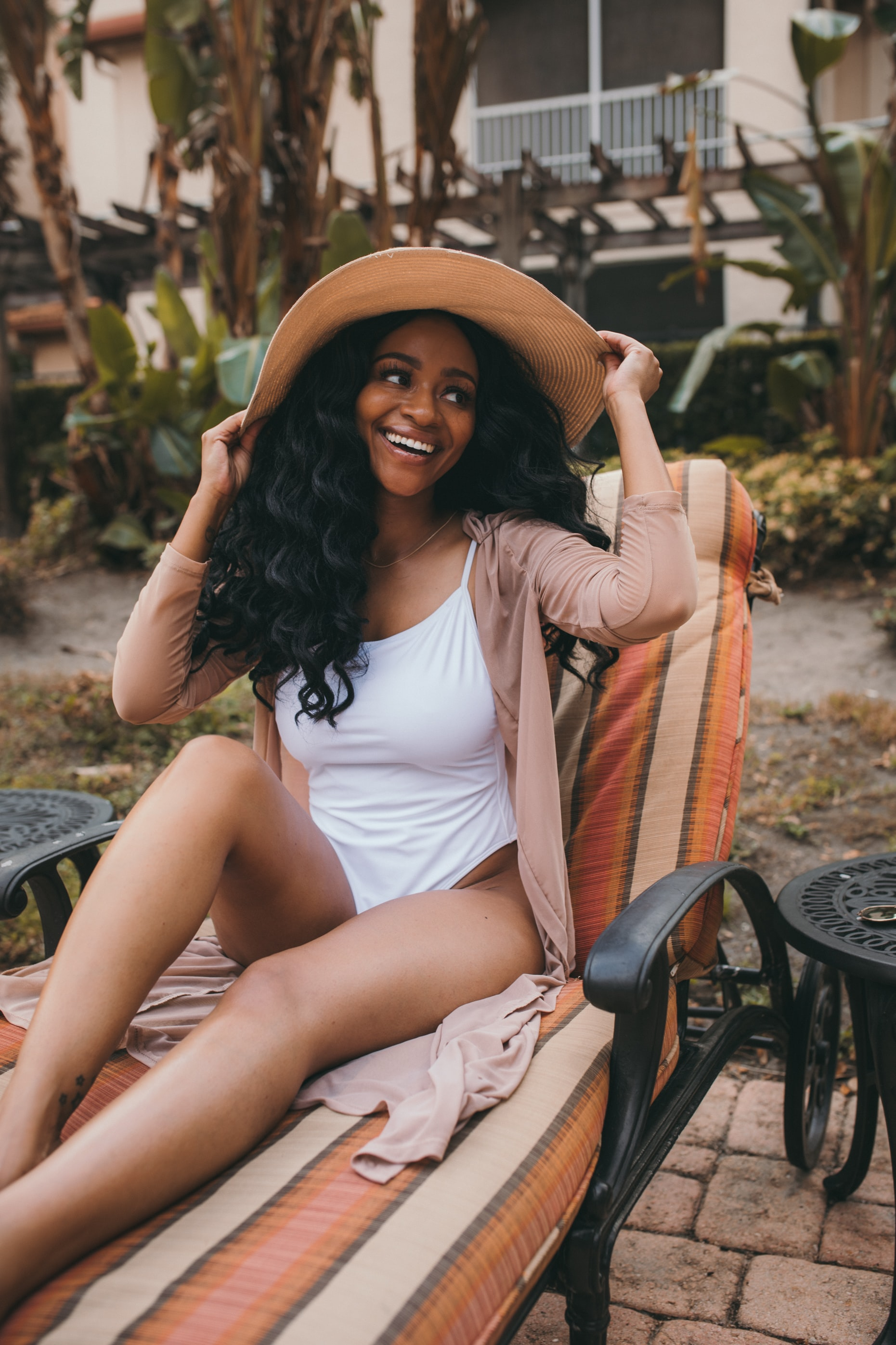 woman in white swimsuit sitting on outdoor lounge smiling