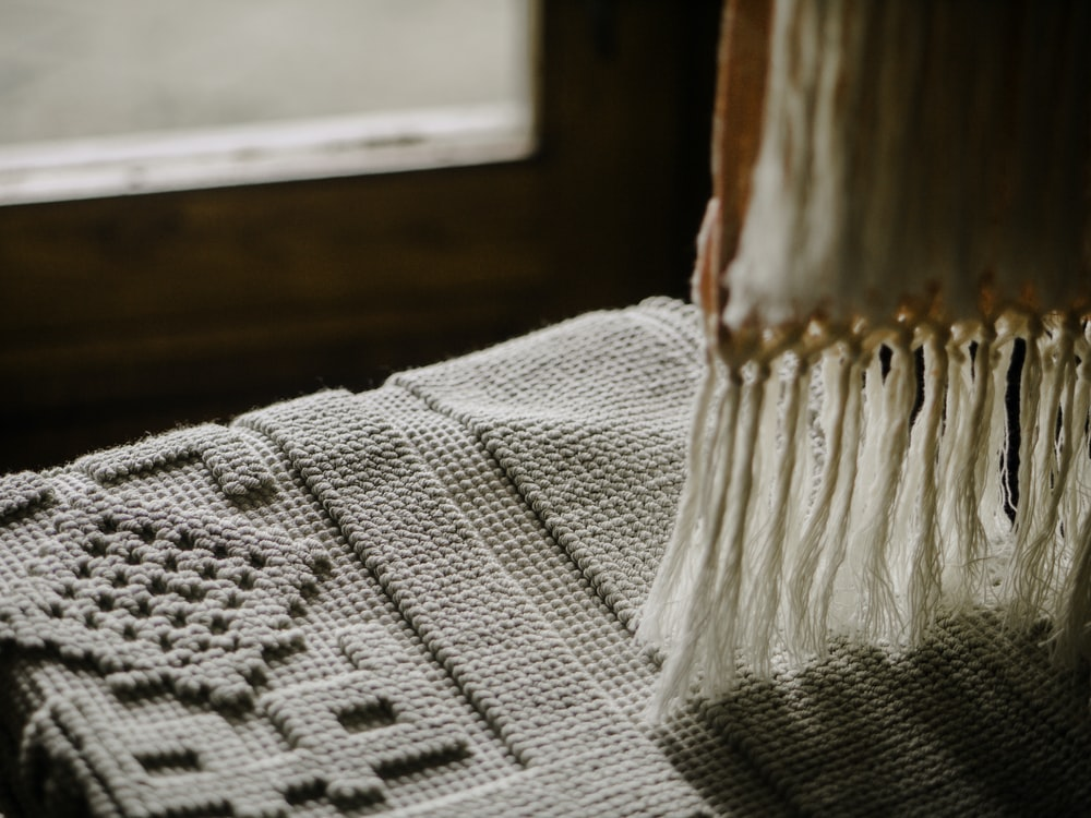 person taking photo of gray textile