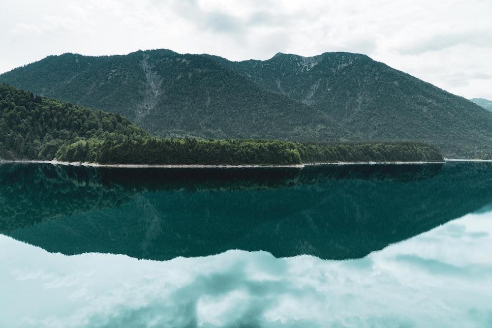calm body of water near mountain