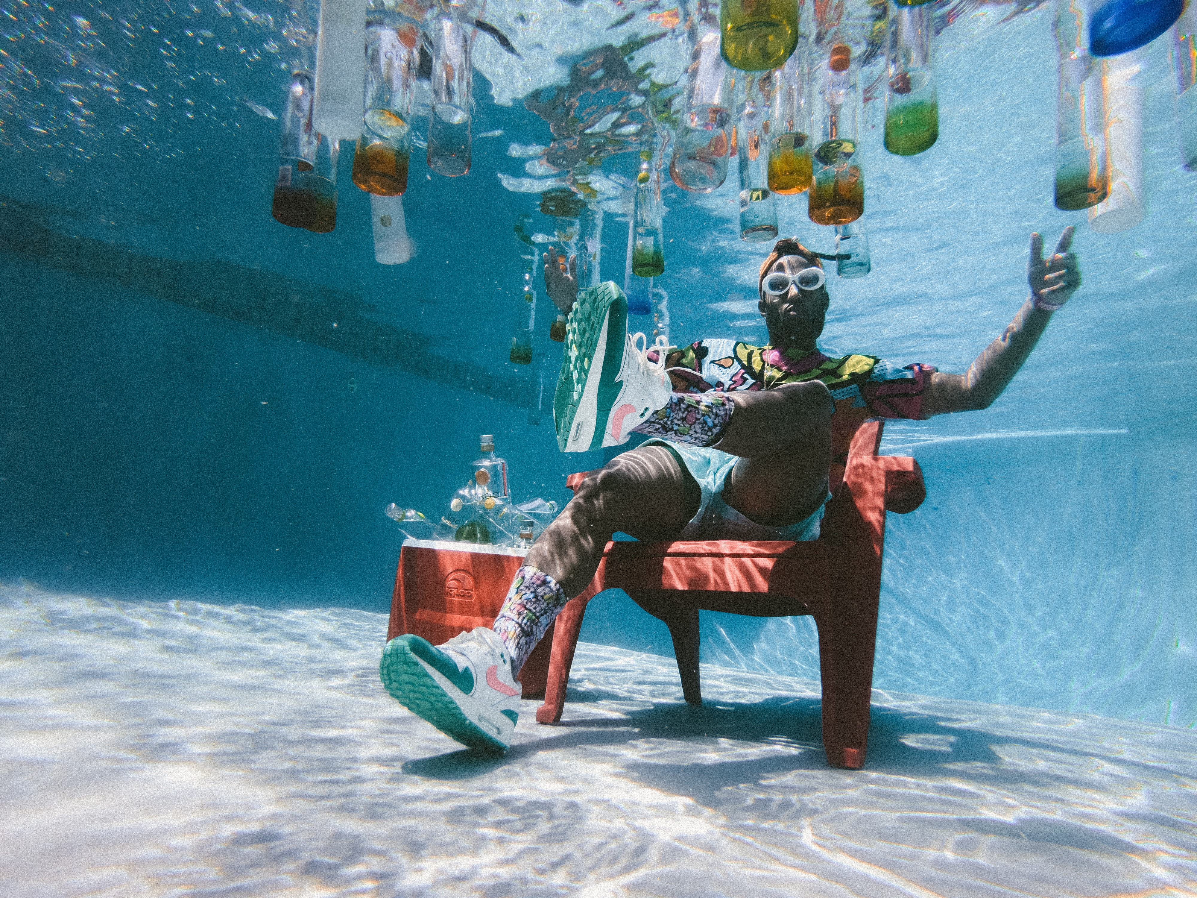 man sitting on chair underwater with floating bottles
