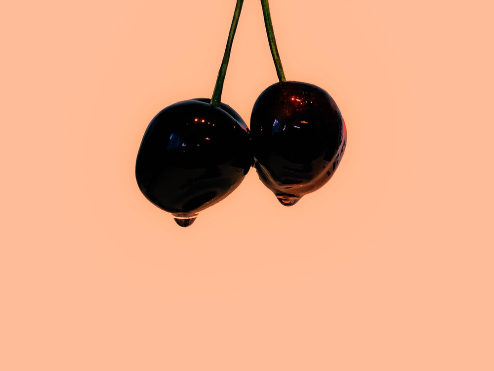 two dipped cherries near pink wall