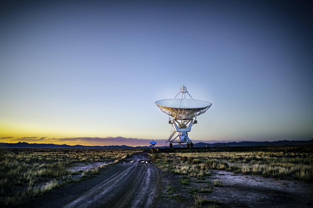 white radar telescope on grass field
