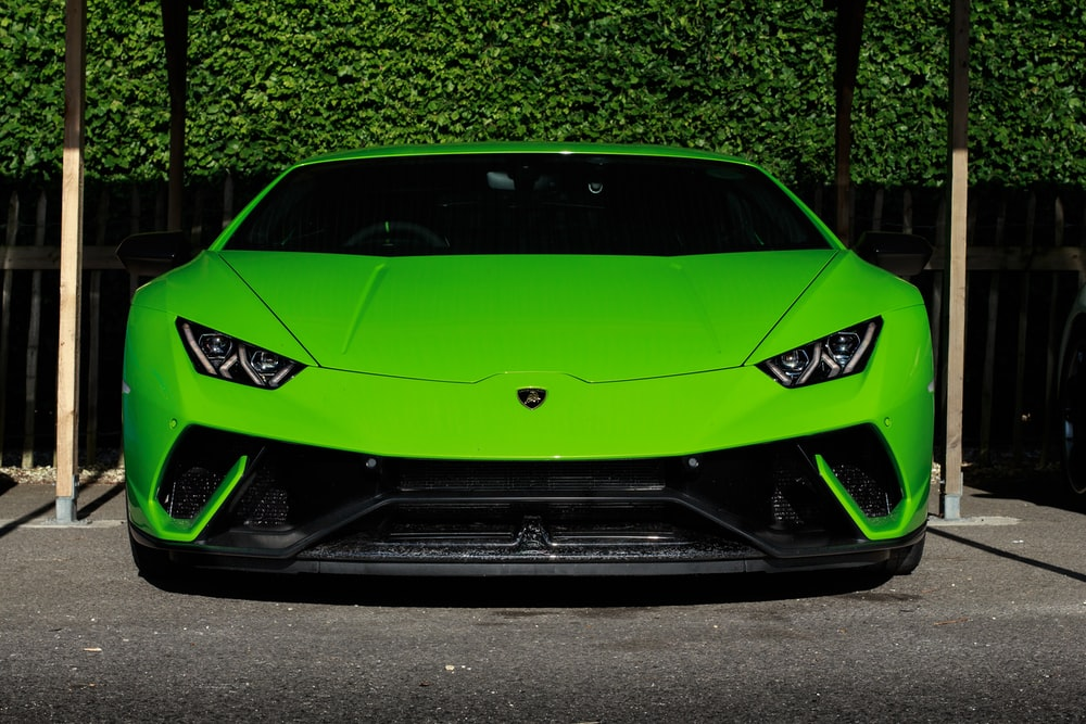 green Lamborghini Huracan sports coupe parked near wooden post