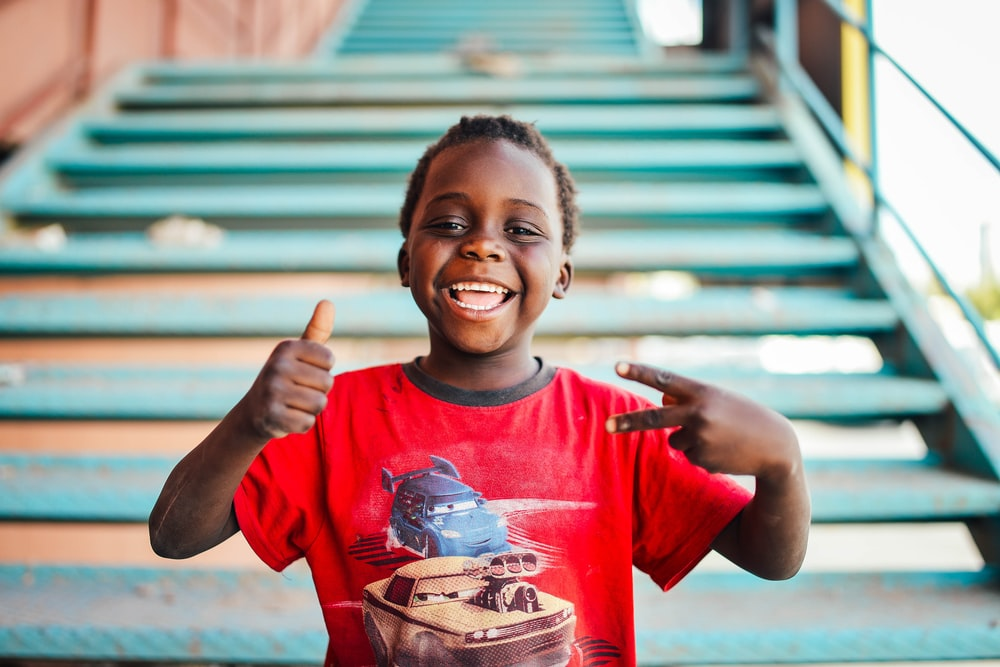 boy standing near stairs doing peace sign at daytime