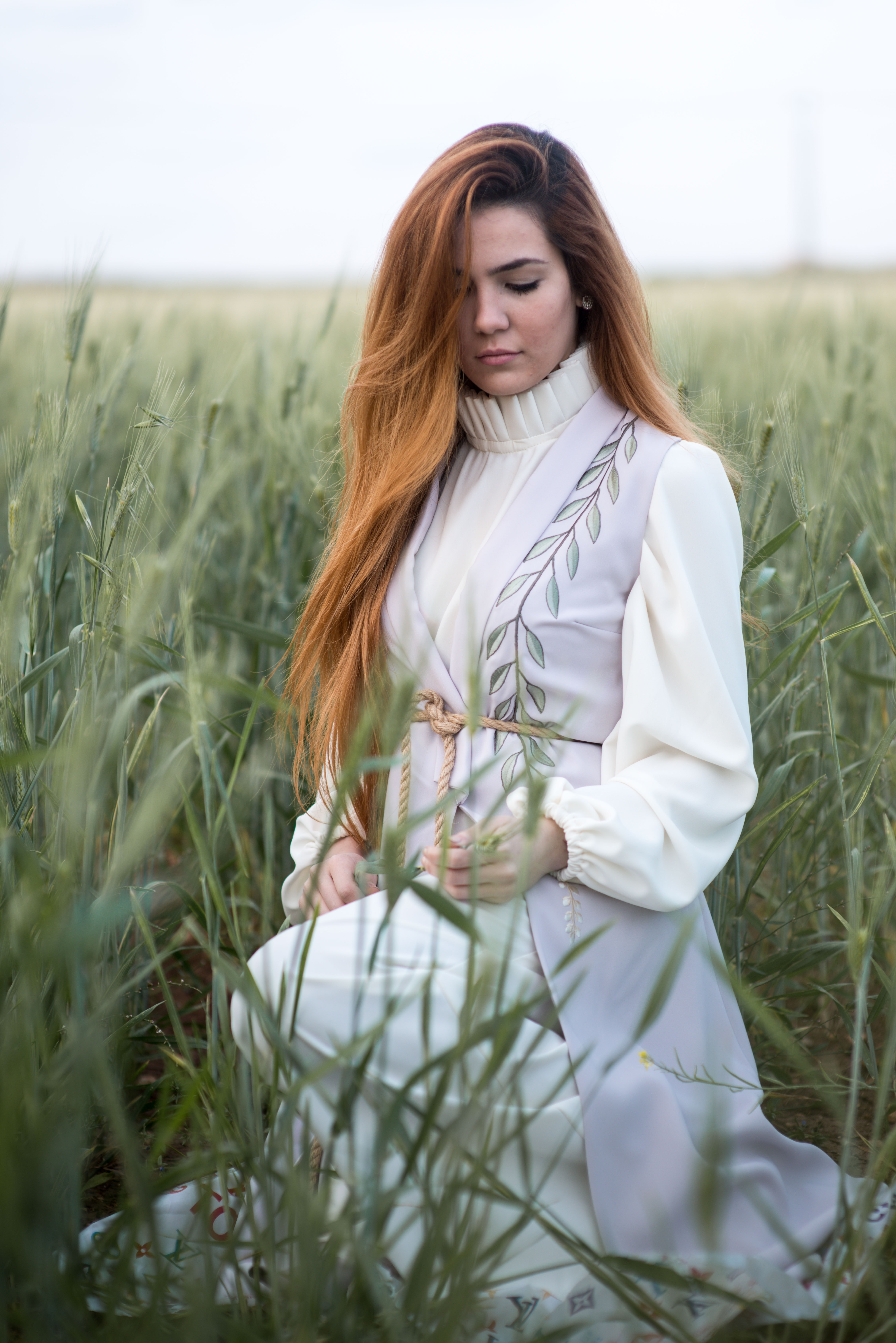 woman in white dress holding green grass during daytime