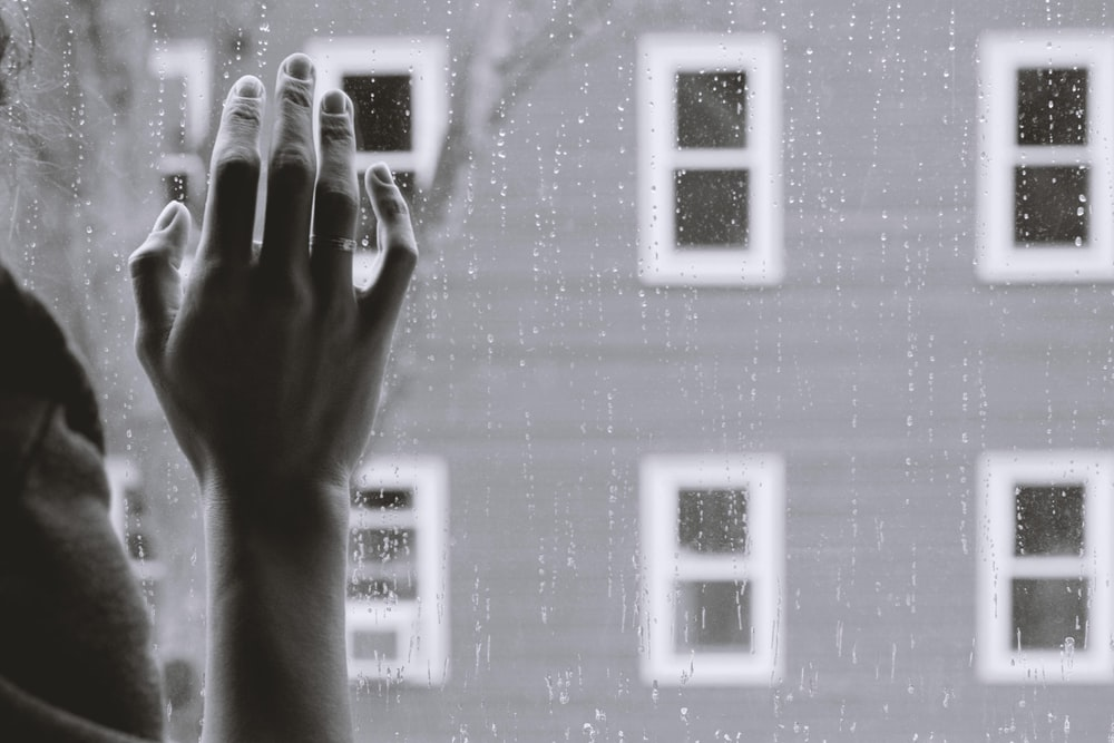 grayscale photo of person holding glass window while raining