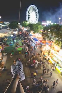 selective focus photo of person wearing sneakers and ferris wheel at distance