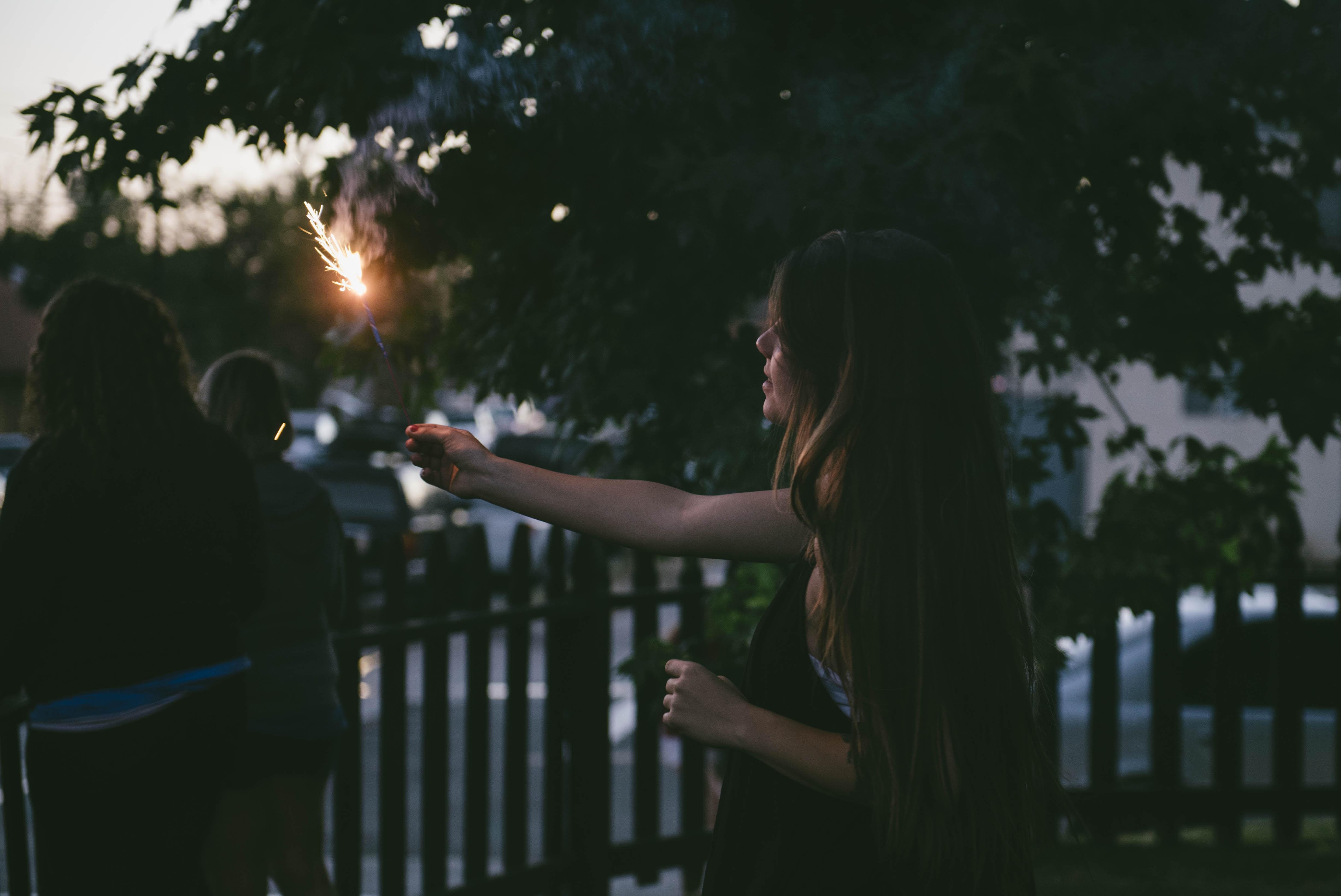 woman holding sparkler near fence