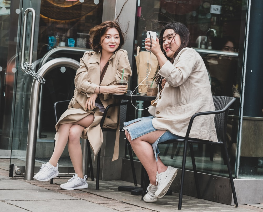 two woman sitting on armchair outside store