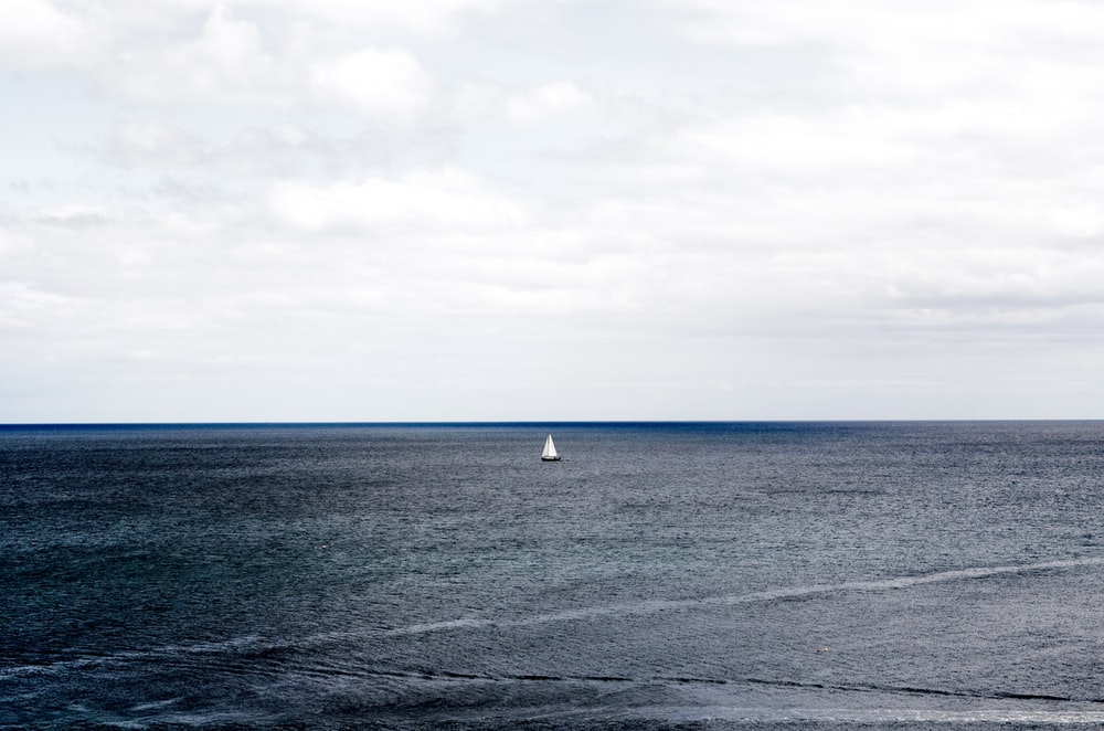 white sailboat on ocean under cloudy sky during daytime