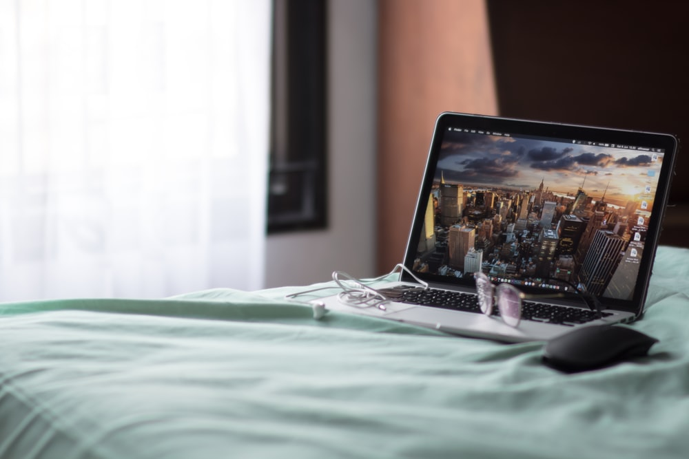 turned-on MacBook Pro on bed