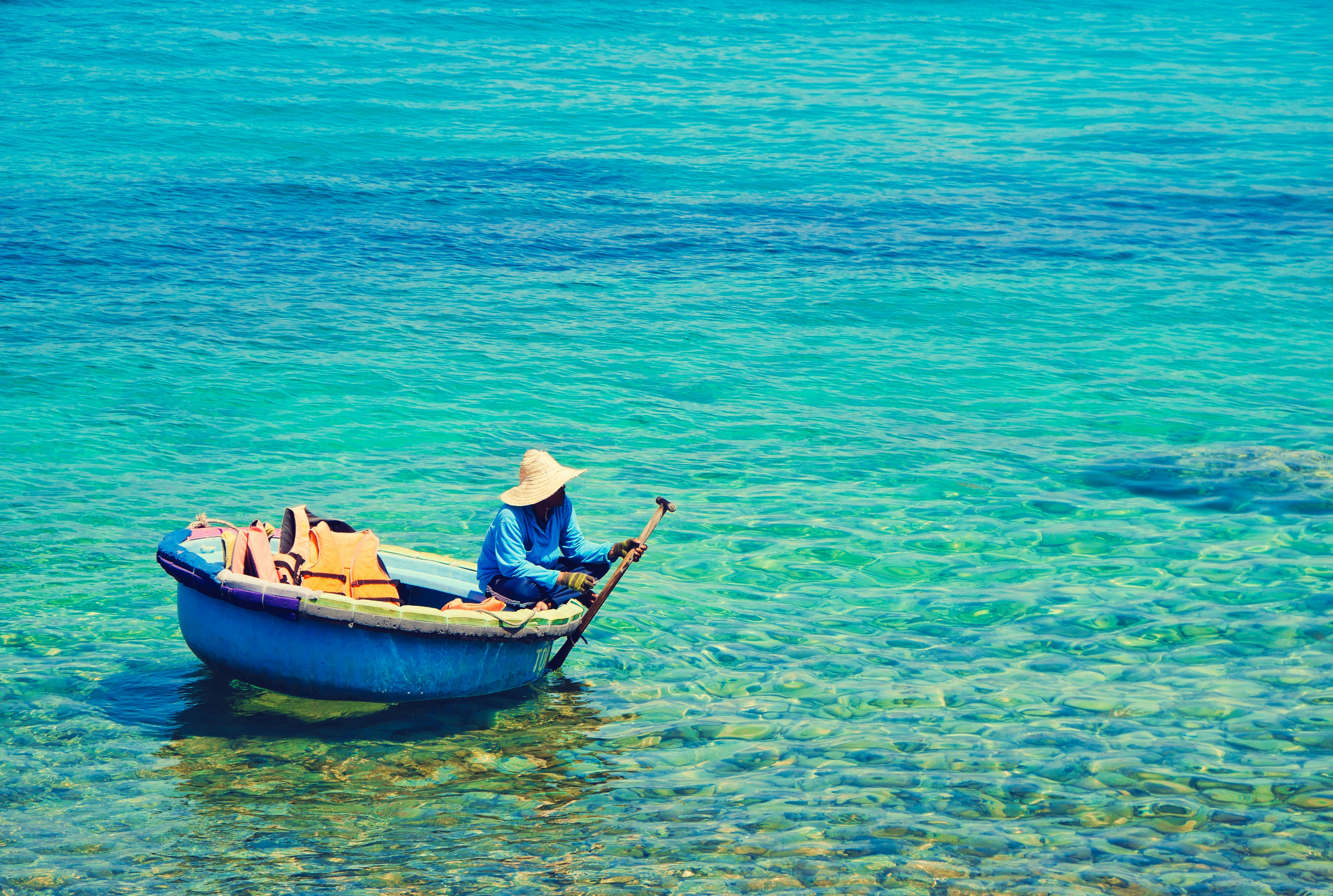 person riding blue boat on body of water