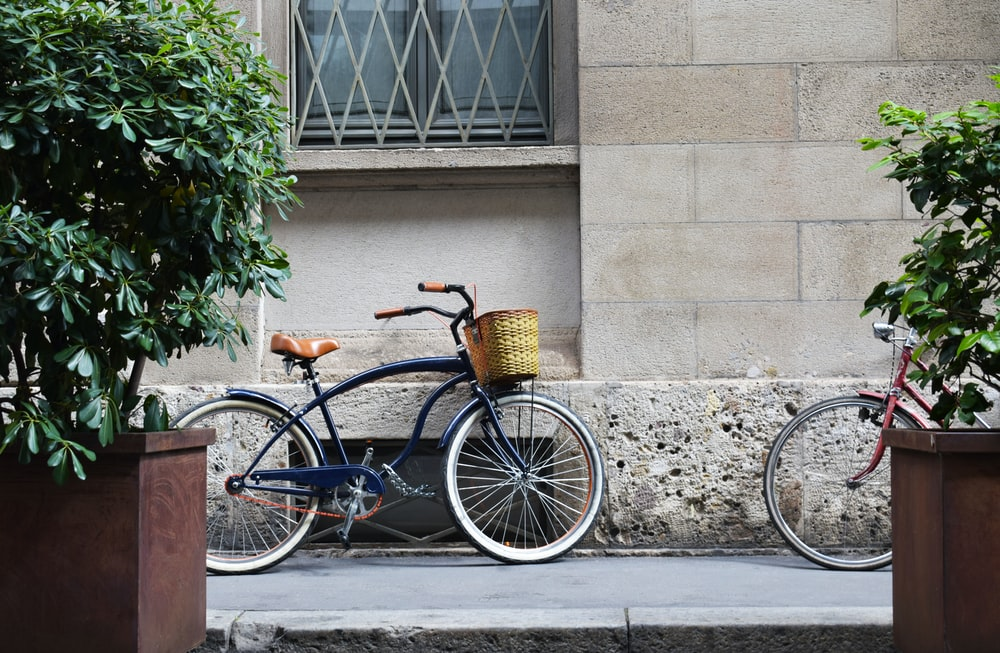 blue bicycle parked upright near building