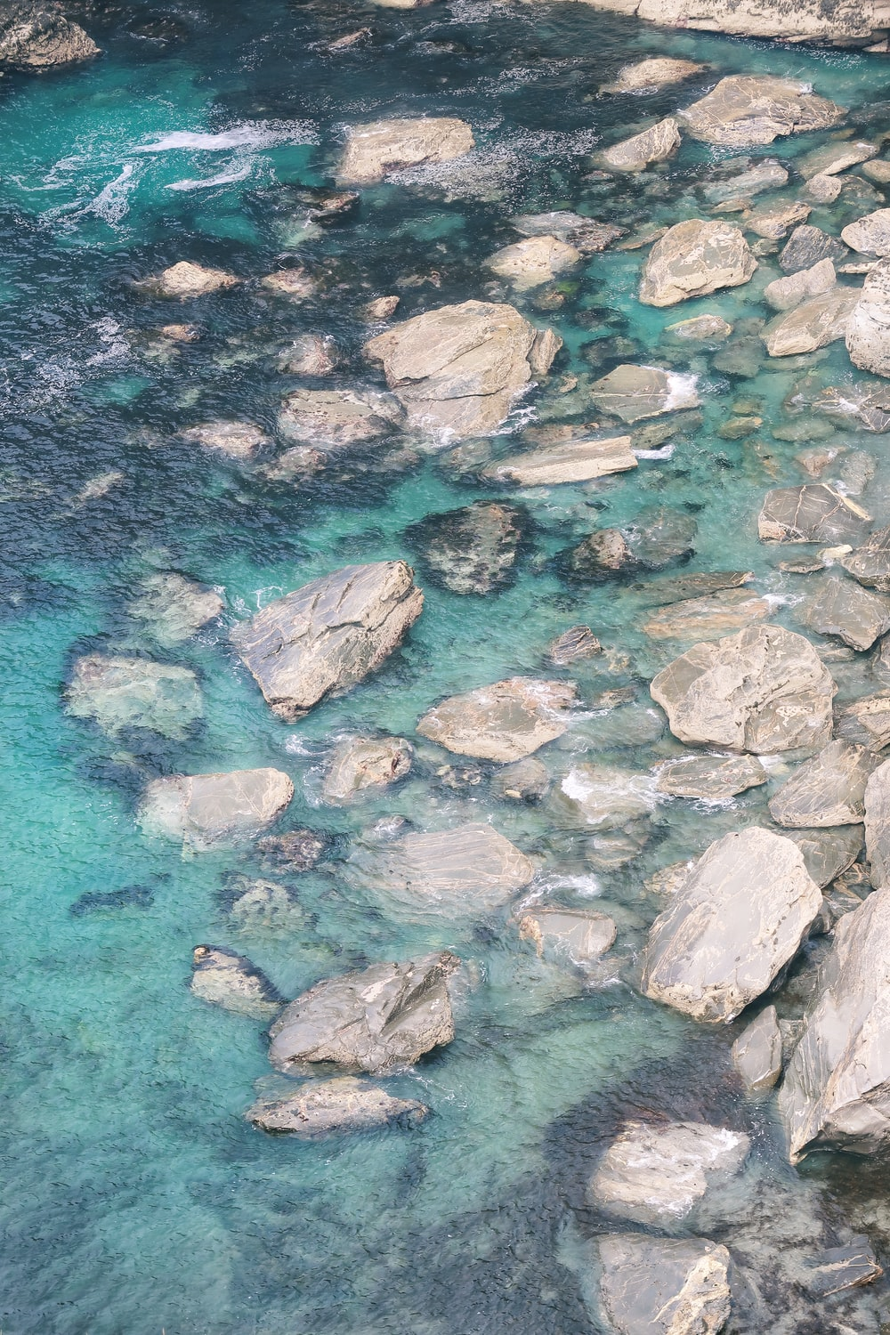 aerial photography of gray rocks and body of water at daytime