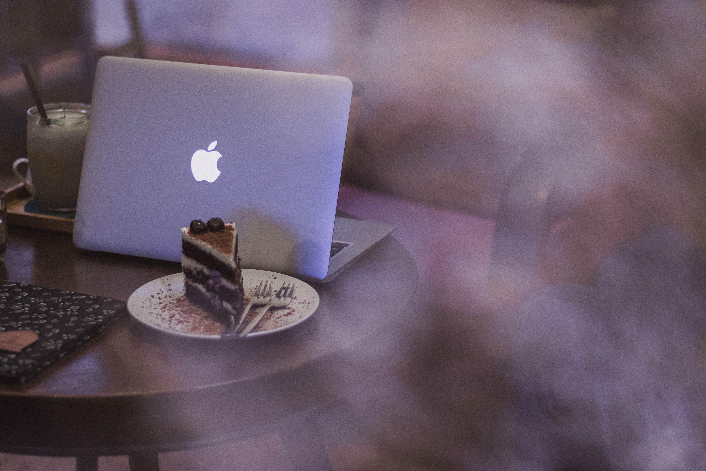 silver MacBook on top of brown table