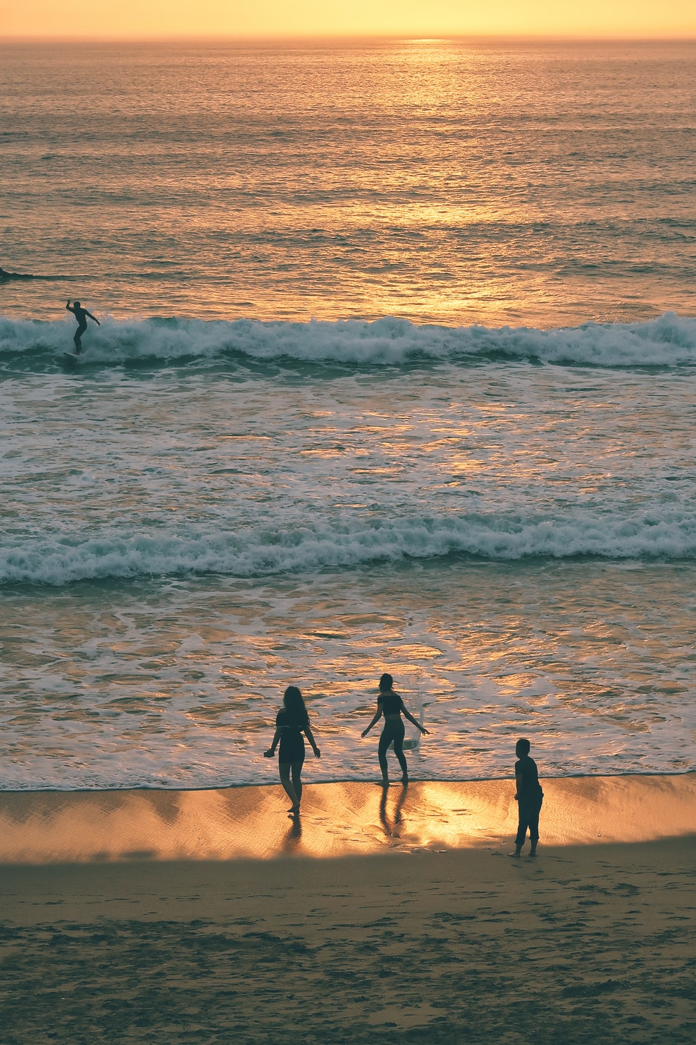 three person walking on sea shore